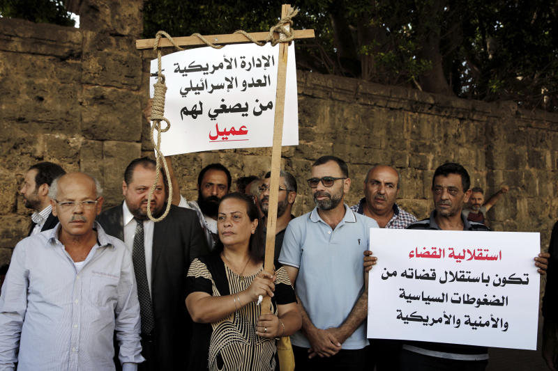 "Former inmates of Khiam prison hold placards in Arabic that read, ""who listens to the American administration and the Israeli enemy. He is an agent,"" left, and ""the independence of justice is when the judiciary is independent from American political and security pressures,"" right, during a sit-in near a military court where an arrest warrant was issued for Lebanese-American Amer Fakhoury, who confessed he'd worked for Israel during its occupation of Lebanon for nearly two decades, in Beirut, Lebanon, Tuesday, Sept. 17, 2019. Fakhoury was detained after returning to his native Lebanon from the United States earlier this month. (AP Photo/Bilal Hussein)"