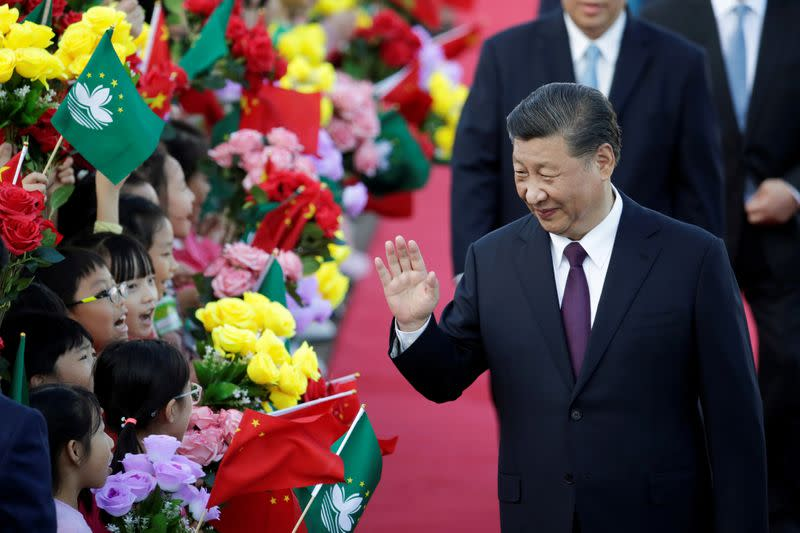 Chinese President Xi Jinping waves at children holding Chinese and Macau flags after arriving at Macau International Airport in Macau