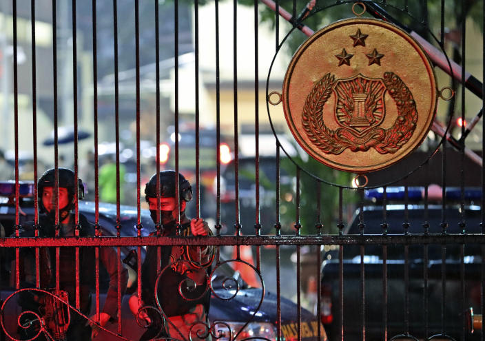 Police officers stand guard at the main gate of the National Police Headquarters following a suspected militant attack in Jakarta, Indonesia, Wednesday, March 31, 2021. A woman entered the Indonesian National Police Headquarters in Jakarta and pointed a gun at several officers before being shot dead by police, in the latest in a series of suspected militant attacks in the world's most populous Muslim nation. (AP Photo/Dita Alangkara)
