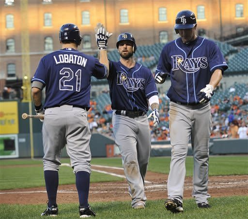 Tampa Bay Rays' Ryan Roberts, center, is congratulated by Jose Lobaton, left, after hitting a two-run home run, scoring Matt Joyce, right, against the Baltimore Orioles in the third inning of a baseball game Wednesday, July 25, 2012, in Baltimore.(AP Photo/Gail Burton)