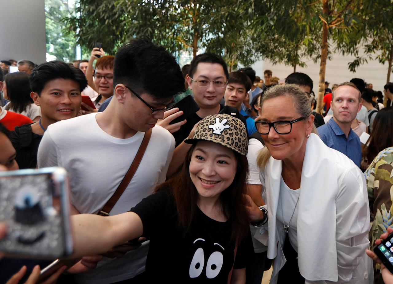 People take selfies with Angela Ahrendts, Apple's Senior Vice President of Retail, at the city-state's first Apple Store on its opening day at Orchard Road, Singapore May 27, 2017. REUTERS/Edgar Su