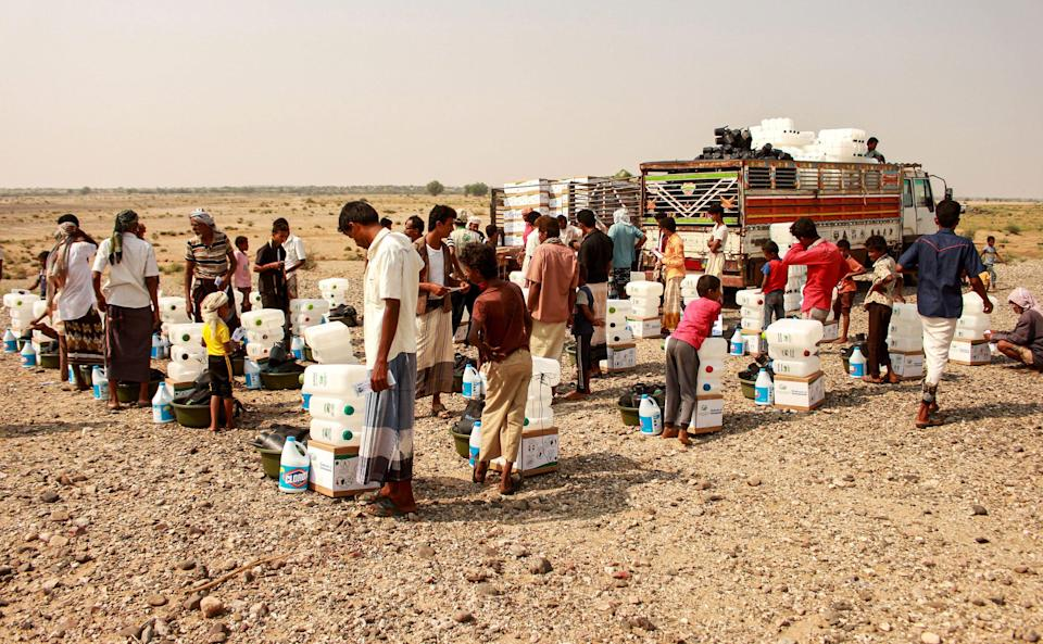 <p>Yemenis displaced by the civil war receiving aid</p> (AFP via Getty Images)