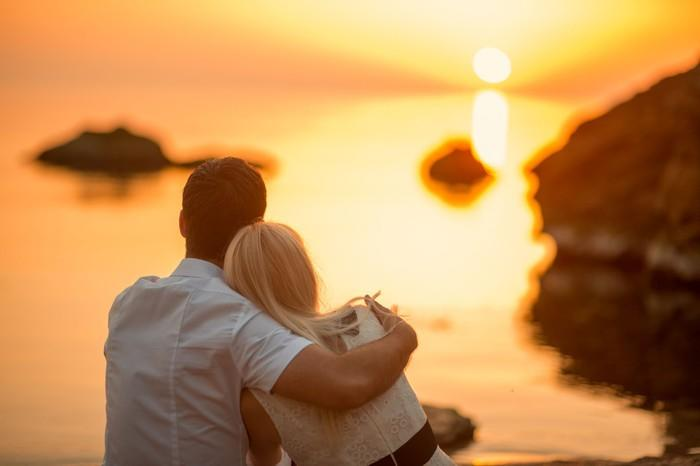 Couple sitting on the beach while watching the sun set.