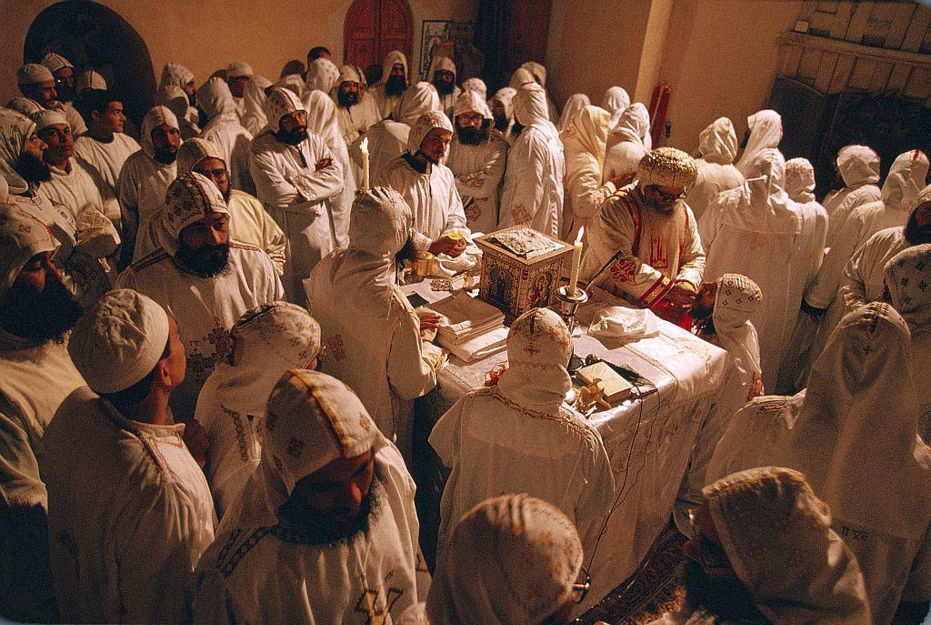EGYPT, NILE DELTA, WADI - NATRUN VALLEY, COPTIC MONASTRY OF ST BISHOY: In deep contemplation, the Coptic monks, wearing white, symbolizing the purity of the angels, kneel around the altar, during the Coptic Christmas ceremony celebrated by Archbishop Sarabamon in the Monastery of St Bishoy on the night of 6th to 7th January, in accordance with the Julian calendar.  File photo: 1996