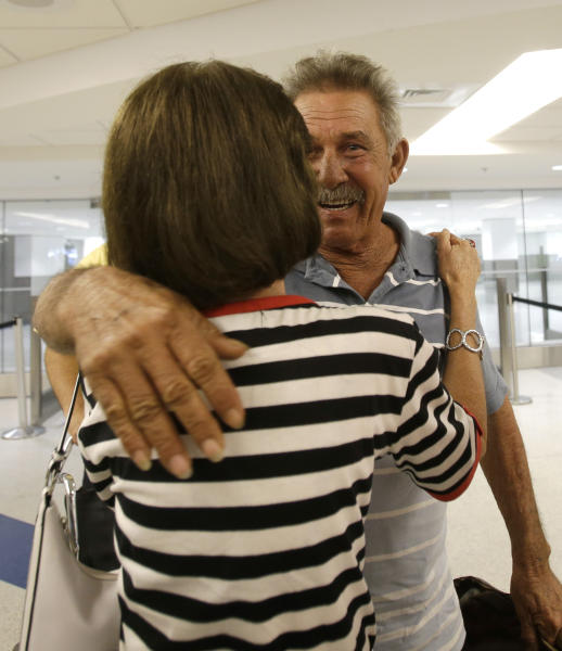 In this Sept. 11, 2013, photo, Benito Perez is welcomed by friend Rogelia Ventura at his arrival at Miami International Airport, in Miami. Perez, who had never been on a plane, is one of thousands of Cubans traveling under new laws making travel slightly easier. (AP Photo/Alan Diaz)