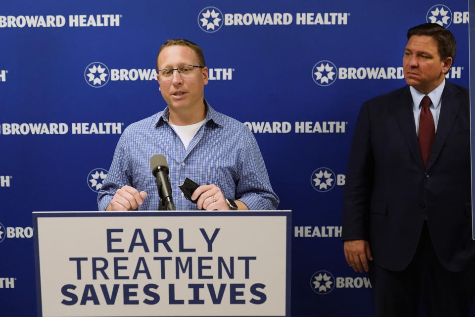Micha Siegel, left, of Boca Raton, Fla., speaks at a news conference about his experience having been treated with monoclonal antibodies after a bout with COVID-19, as Florida Gov. Ron DeSantis, right, listens, Thursday, Sept. 16, 2021, at the Broward Health Medical Center in Fort Lauderdale, Fla. DeSantis was there to promote the use of monoclonal antibody treatments for those infected with COVID-19. (AP Photo/Wilfredo Lee)