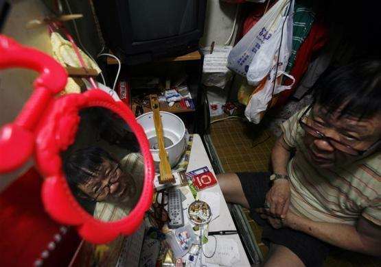 "A man sits inside his ""cubicle"" home, one of the 19 24-square feet units inside a 600 square foot residential apartment complex in Hong Kong September 16, 2009. The Hong Kong government estimates that about 100,000 people live in similar ""cubicle"" units, which cost an average monthly rental rate of $150, in one of the world's largest financial hubs, according to the Society for Community Organization, an NGO which helps those in need."