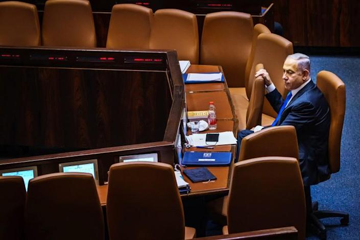 Outgoing Prime Minister Benjamin Netanyahu takes a look around the empty seats as members of the Knesset, Israel's parliament, step out for a break before returning to cast their vote of confidence to empower the new coalition government and unseat Netanyahu on Sunday. (Marcus Yam / Los Angeles Times)