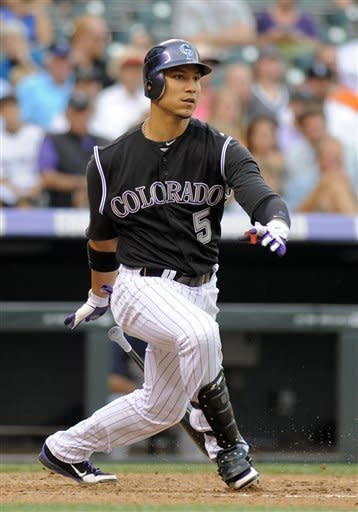 Colorado Rockies' Carlos Gonzalez watches his RBI triple off San Diego Padres starting pitcher Jason Marquis during the sixth inning of a baseball game in Denver, Friday, June 29, 2012. Gonzalez scored on the play after an error. (AP Photo/Jack Dempsey