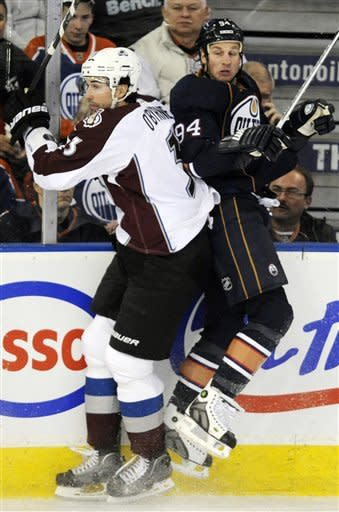 Colorado Avalanche's Ryan O'Byrne, left, checks Edmonton Oilers' Ryan Smyth during the first period of an NHL hockey game, Tuesday, Jan. 31, 2012, in Edmonton, Alberta. (AP Photo/The Canadian Press, John Ulan)