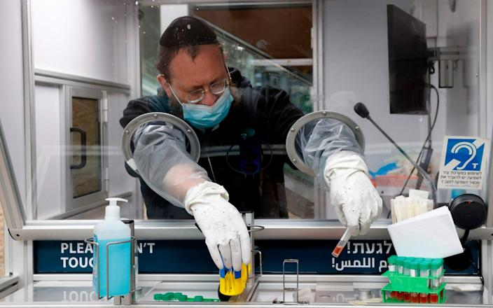 A medic collects a swab sample from a traveller at a booth at the COVID-19 coronavirus rapid testing centre in Israel's Ben-Gurion Airport - AFP