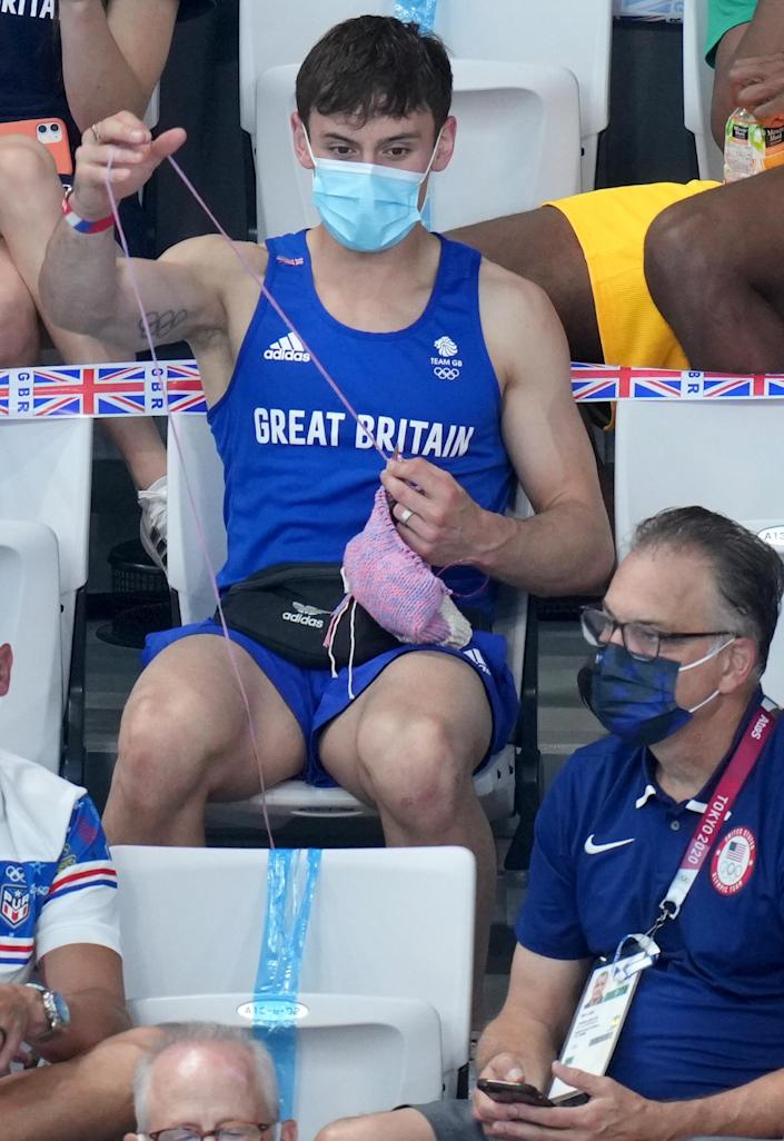 Tom Daley knits in the stands. (Joe Giddens / PA Images / Getty Images)