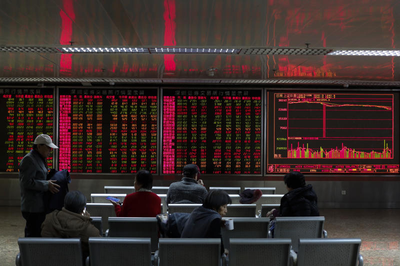 Chinese investors monitor stock prices at a brokerage house in Beijing, Friday, Dec. 6, 2019. Shares swung higher in Asia on Friday after a wobbly day of trading on Wall Street as investors awaited a U.S. government jobs report and kept an eye out for developments in China-U.S. trade talks. (AP Photo/Andy Wong)