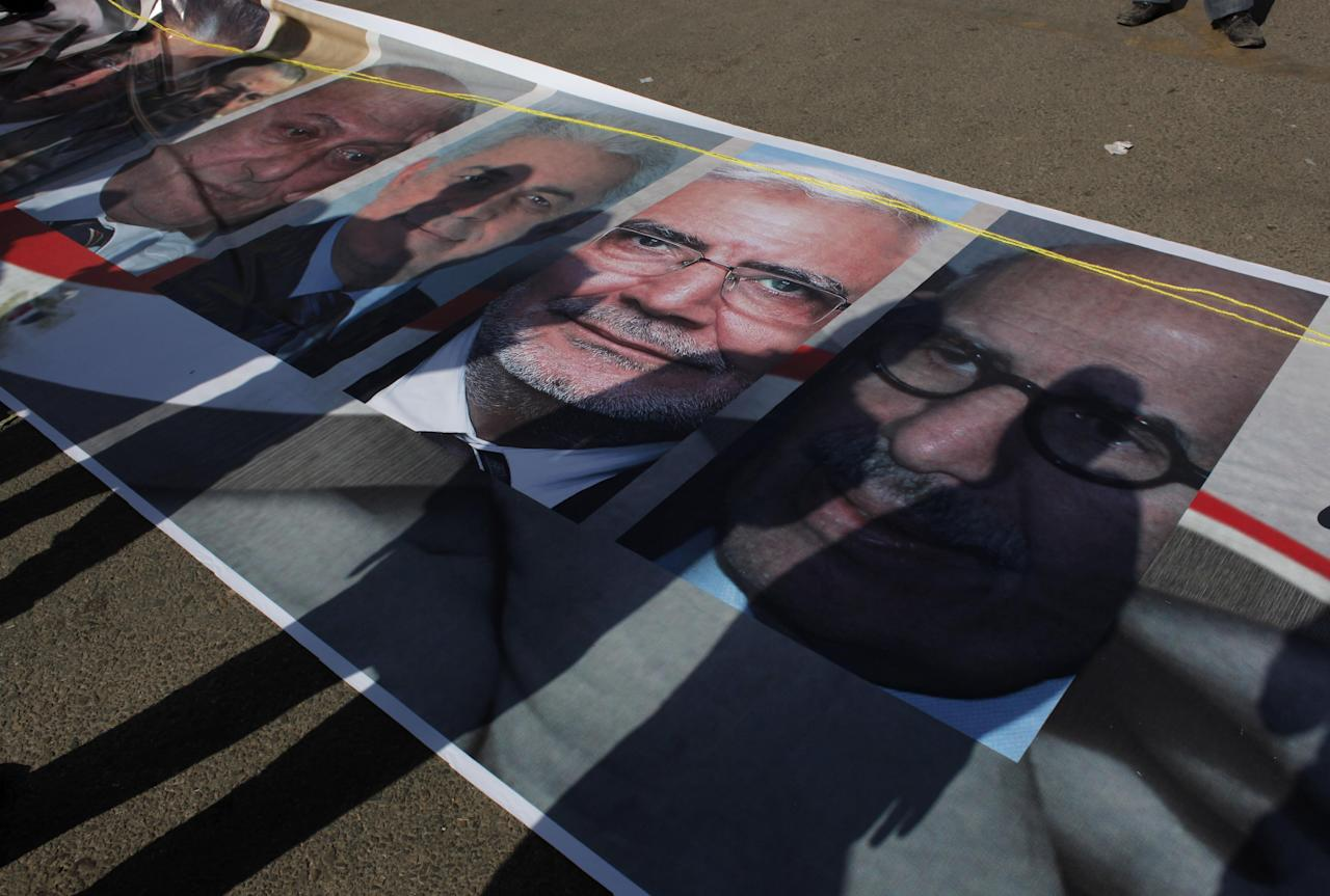 The shadows of Egyptian activists are seen on a banner with pictures of Egyptian politicians and presidential hopefuls as it is being prepared for display, during a rally at Tahrir square, Cairo, Egypt, Friday, April 20, 2012. Pictures from right, Egyptian pro-democracy advocate Mohamed ElBaradei, presidential hopeful Abdel-Moneim Abolfotoh and presidential hopeful Hamdin Sabbahi. (AP Photo/Nasser Nasser)