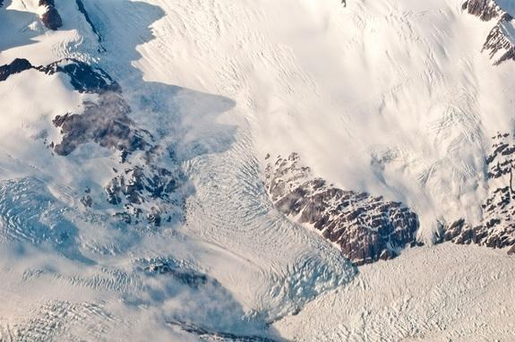 The heavily crevassed ice on this small Greenland outlet glacier cascades down to the fjord water (bottom right), which is filled with icebergs and small bits of ice.