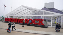 People walk past the Rock & Roll Hall of Fame where the red carpet for the NFL Draft will be held, Saturday, April 24, 2021, in Cleveland. Forced to cancel last year's event in Las Vegas, the league is using lessons learned while plowing through an unprecedented, socially-distanced 2020 season and holding the Super Bow in Tampa, to have a draft that will look much more like normal — well, the new normal — with fans wearing their favorite team's colors and required masks. (AP Photo/Tony Dejak)