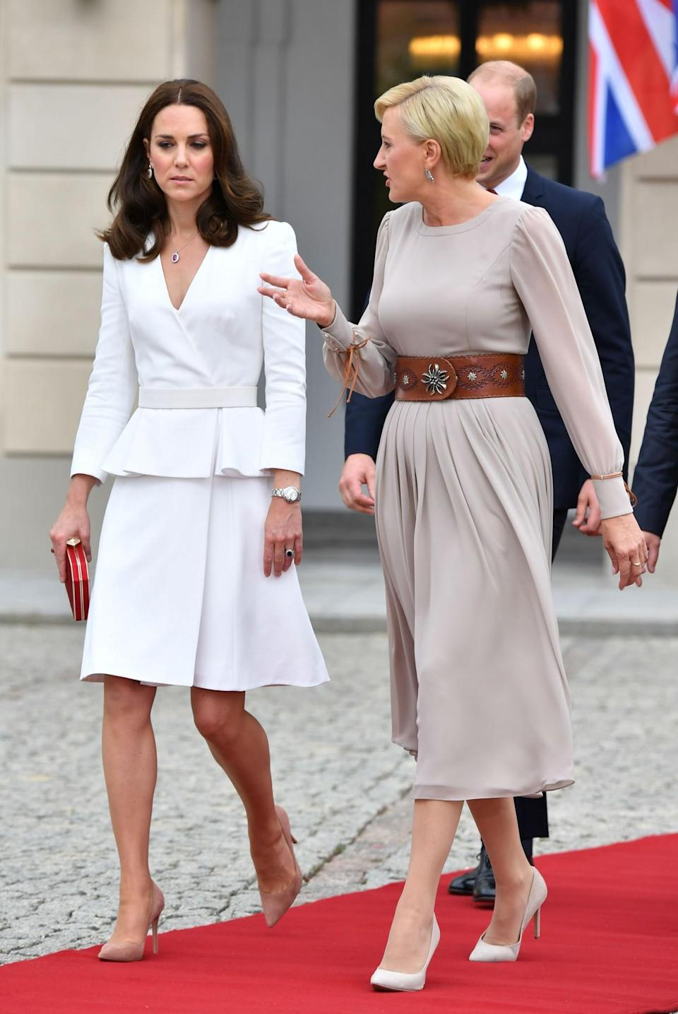 <p><b><b><b>The Duchess swapped her post-plane journey accessory, Princess Charlotte, for a boxy red Jenny Packham clutch as she chatted with the First Lady of Poland at Warsaw's Presidential Palace. <em>[Photo: PA]</em> </b></b></b></p>