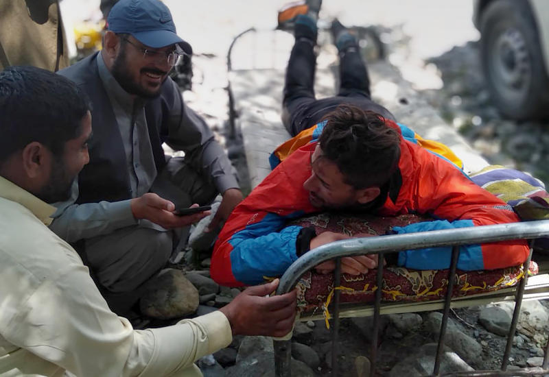 In this photo provided by Gilgit Baltistan regional police department, a mountaineer receives initial treatment following his rescue, at a helipad in the town of Imit, Ghizer district of Gilgit Balistan region, Pakistan, Tuesday, Jun 18, 2019. A Pakistani army helicopter rescued on Tuesday four Italian and two Pakistani climbers stranded at an altitude of around 5,300 meters (17,390 feet) in the country's north, after an avalanche struck the team the previous day, a mountaineering worker said. A Pakistani member of the team was killed. (Gilgit Baltistan regional police department via AP)
