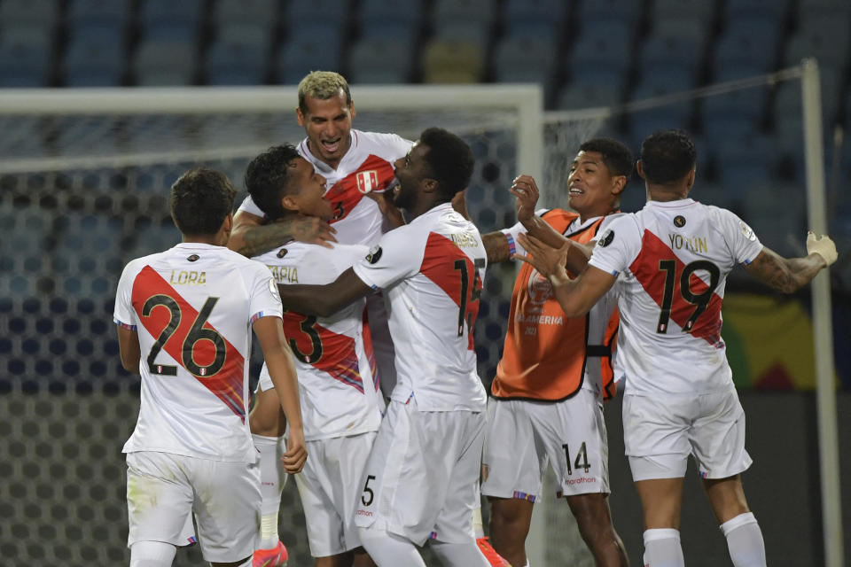 Peru's Miguel Trauco (C) celebrates with teammates after scoring the winning goal during the penalty shootout of the Conmebol 2021 Copa America football tournament quarter-final match between Peru and Paraguay at the Olympic Stadium in Goiania, Brazil, on July 2, 2021. (Photo by NELSON ALMEIDA / AFP) (Photo by NELSON ALMEIDA/AFP via Getty Images)