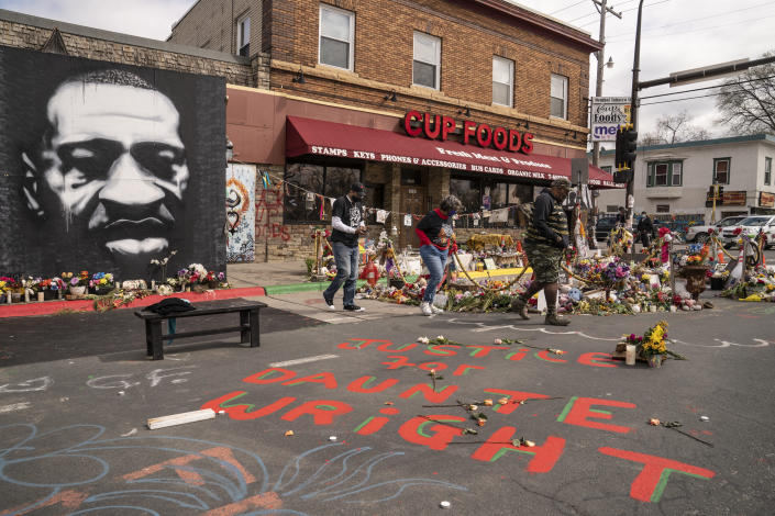 Visitors browse a memorial to George Floyd as a new addition commemorating Daunte Wright is displayed outside Cup Foods, Wednesday, April 14, 2021, in Minneapolis, Minn. (AP Photo/John Minchillo)