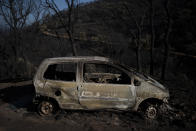 A car burnt by wildfires is pictured in Val de Gilly, southern France, Thursday, Aug. 19, 2021. A fire that has ravaged forests near the French Riviera for four days is slowing down as winds and hot weather subside, but more than 1,100 firefighters were still struggling to get it under control Thursday, local authorities said. (AP Photo/Daniel Cole)