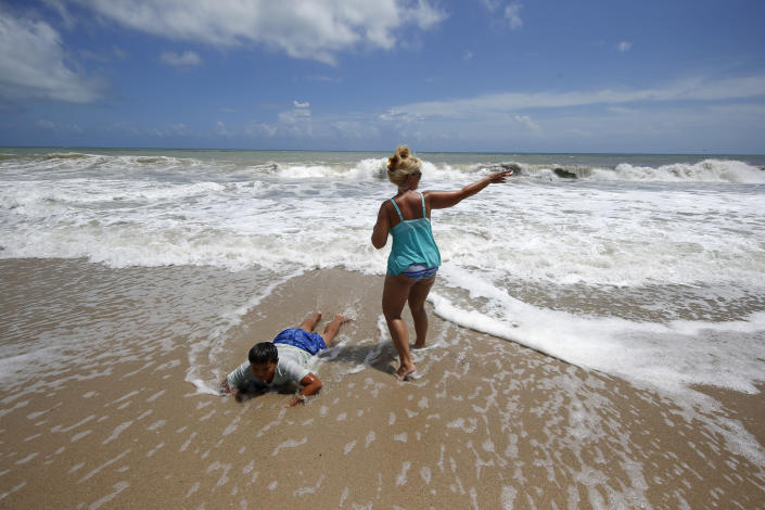 Tenille Choi and her son Remington Choi play in the high surf form the Atlantic Ocean on the barrier island in Vero Beach, Fla., Sunday, Sept. 1, 2019. The barrier island is under a voluntary evacuation today and a mandatory evacuation tomorrow in preparation for the possibility of Hurricane Dorian making landfall. (AP Photo/Gerald Herbert)