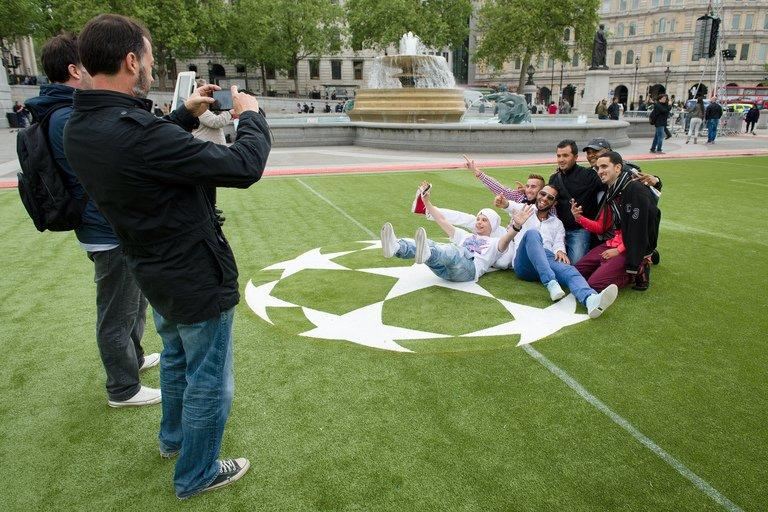 People take photos in a 'football fan zone' at Trafalgar Square in London, on May 22, 2013