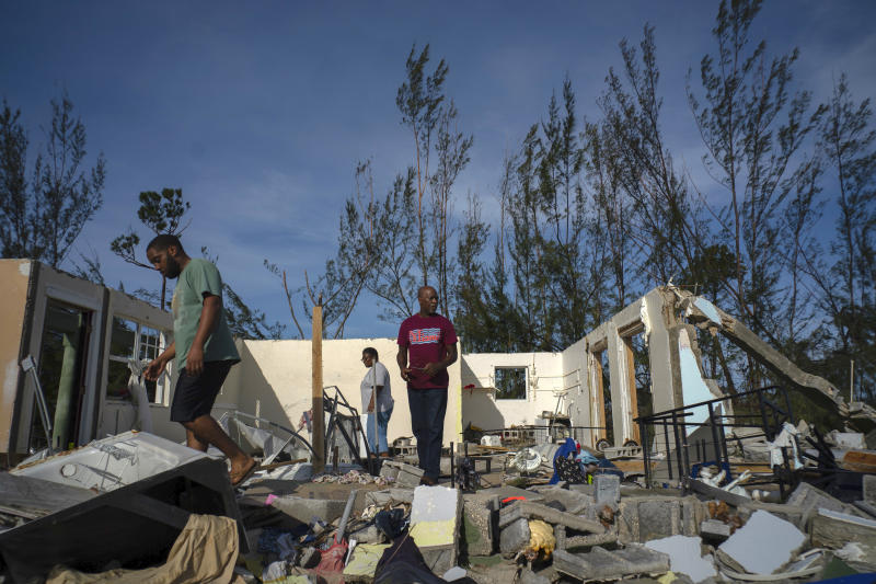 George Bolter, left, and his parents walk through the remains of his home destroyed by Hurricane Dorian in the Pine Bay neighborhood of Freeport, Bahamas, Sept. 4, 2019. (Photo: Ramon Espinosa/AP)