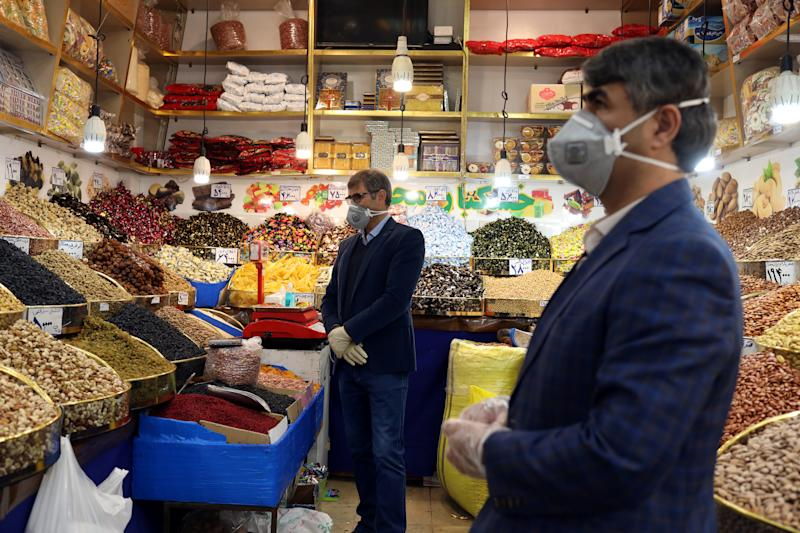 Men wear protective face masks and gloves, following the outbreak of coronavirus, as they are seen in a nuts shop in Tehran