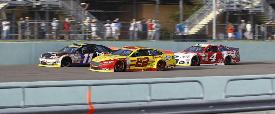 Denny Hamlin (11), Joey Logano (22) and Kevin Harvick race each other during the NASCAR Sprint Cup championship series auto race, Sunday, Nov. 16, 2014 in Homestead, Fla. (AP Photo/Terrry Renna)