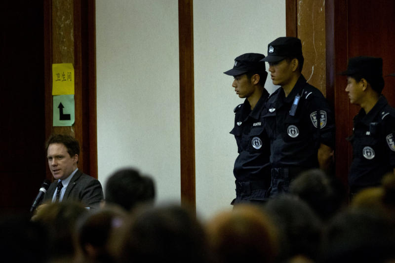 Policemen guard their positions near a translator, left, during a meeting between Malaysian officials and relatives of Chinese passengers onboard the missing Malaysia Airlines Flight 370 at a hotel in Beijing, China, Wednesday, April 30, 2014. The Australian agency heading up the search for the missing Malaysian jet has dismissed a claim by a resource survey company that it found possible plane wreckage in the northern Bay of Bengal. (AP Photo/Alexander F. Yuan)