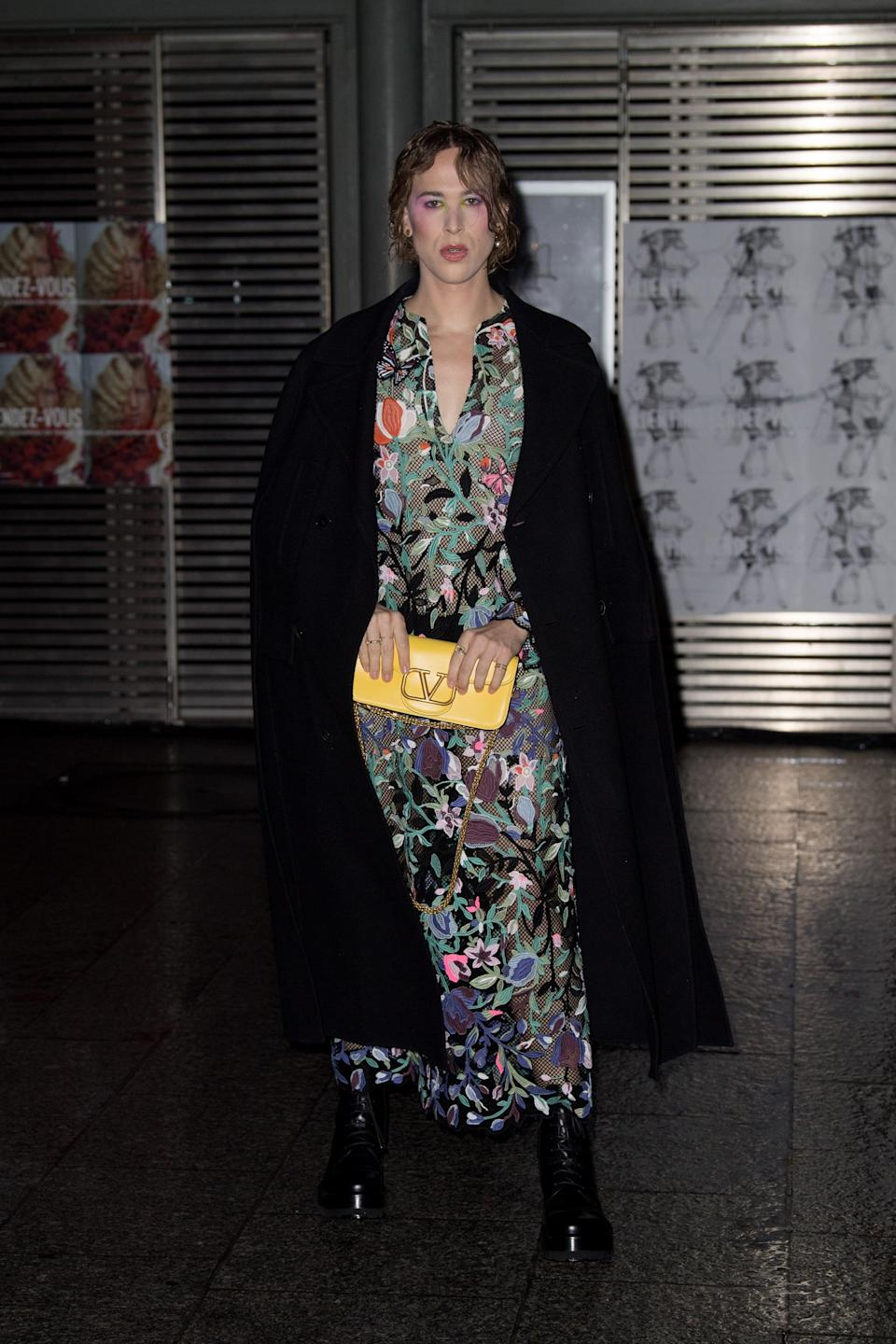 <p>She wore a subtly sheer floral dress, bright yellow clutch, boots, and long coat draped over her shoulders.</p>