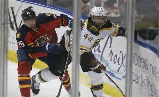 Florida Panthers' Mikael Samuelsson (26) and Boston Bruins' Dennis Seidenberg (44) battle for the puck during the second period of a NHL hockey game in Sunrise, Fla., Thursday, March 15, 2012. (AP Photo/J Pat Carter)
