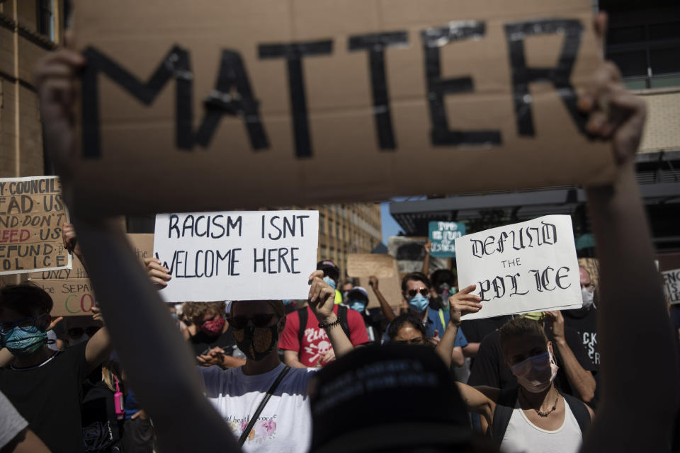 Protesters hold signs during a demonstration calling for the defunding of the police department Saturday, June 13, 2020, in Philadelphia, over the death of George Floyd, who died last month after being restrained by Minneapolis police officers. (AP Photo/David Goldman)