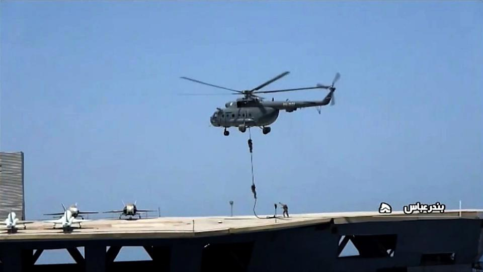 Commandos rappelled down onto the mock US aircraft carrier (IRIB NEWS AGENCY/AFP via Getty I)