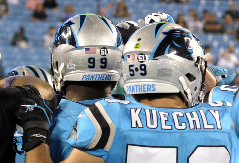 Carolina Panthers' Luke Kuechly (59) and Kawann Short (99) wear a #51 decal on their helmets as they warm up before an NFL football game against the Philadelphia Eagles in Charlotte, N.C., Thursday, Oct. 12, 2017. The 51 is in honor of former Carolina Panthers linebacker and coach Sam Mills, who died of cancer. (AP Photo/Mike McCarn)
