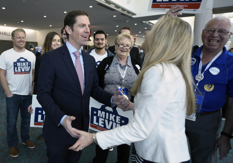 Democratic congressional candidate Mike Levin, left, talks with his wife Chrissy Levin in front of supporters at the 2018 California Democrats State Convention Saturday, Feb. 24, 2018, in San Diego. (AP Photo/Denis Poroy)