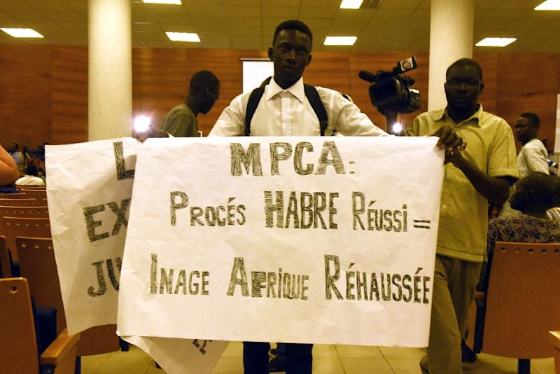 "Protestors hold a banner reading ""MPCA: successful Habre trial = enhanced image of Africa"" in the courtroom during the first proceedings of the trial of Chadian dictator Hissene Habre by the Extraordinary African Chambers in Dakar, July 20, 2015 (AFP Photo/Seyllou)"