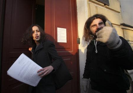 Greenpeace activist Faiza Oulahsen (L) from the Netherlands holds papers certifying the termination of prosecution after walking out of the offices of the Federal Migration Service Department in St. Petersburg, December 25, 2013. REUTERS/Stringer