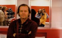 """<p>Director Stanley Kubrick and his daughter, Vivian Kubrick, are photographed in a mirror behind a blurred out Jack Nicholson on the set of the horror movie adapted from the Stephen King novel, <a href=""""https://www.amazon.com/Shining-Stephen-King/dp/0307743659"""" rel=""""nofollow noopener"""" target=""""_blank"""" data-ylk=""""slk:The Shining"""" class=""""link rapid-noclick-resp"""">The Shining</a>. </p>"""