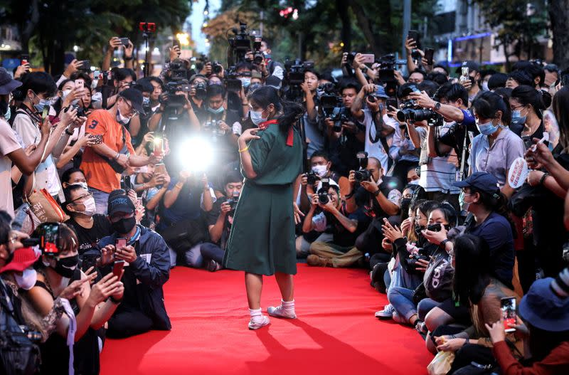 A protester performs on a red carpet while taking part in a protest against the government and to reform monarchy in Bangkok