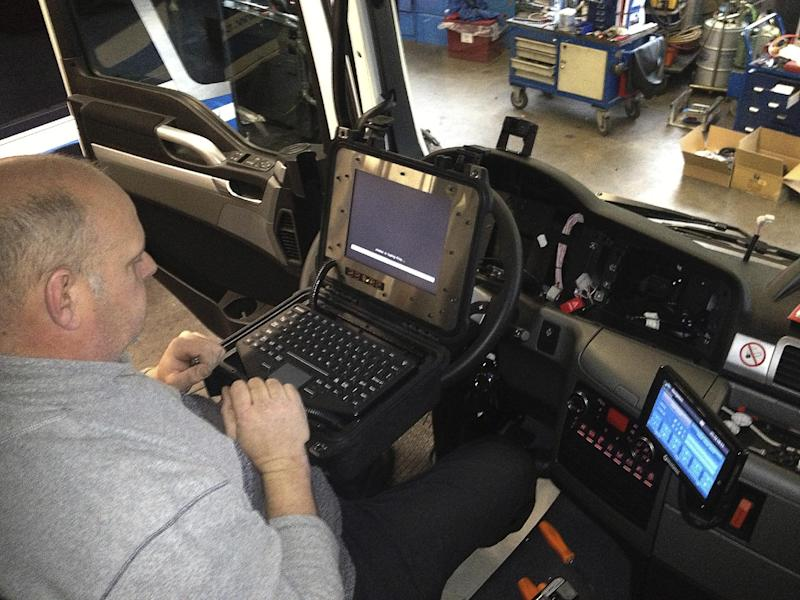 In this handout photo provided by Royal Beuk BV in Noordwijk, Netherlands on Tuesday Dec. 10, 2013 an engineer outfits a bus with a fatigue monitoring system. A Dutch luxury bus company is helping introduce a monitoring technology that has been gaining ground in the mining industry. Royal Beuk BV said Tuesday it is outfitting 20 vehicles from five bus companies with a system designed by Australian company Seeing Machines. It uses infrared lights and a camera to register eye movements for signs a driver may be close to nodding off, and sounds an alarm. (AP Photo/Royal Beuk BV)