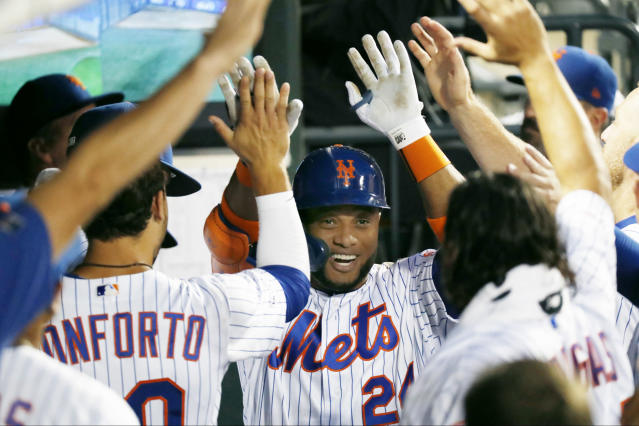 Teammates congratulate New York Mets' Robinson Cano, center, after he hit a solo home run during the fourth inning of a baseball game against the San Diego Padres, Tuesday, July 23, 2019, in New York. (AP Photo/Kathy Willens)