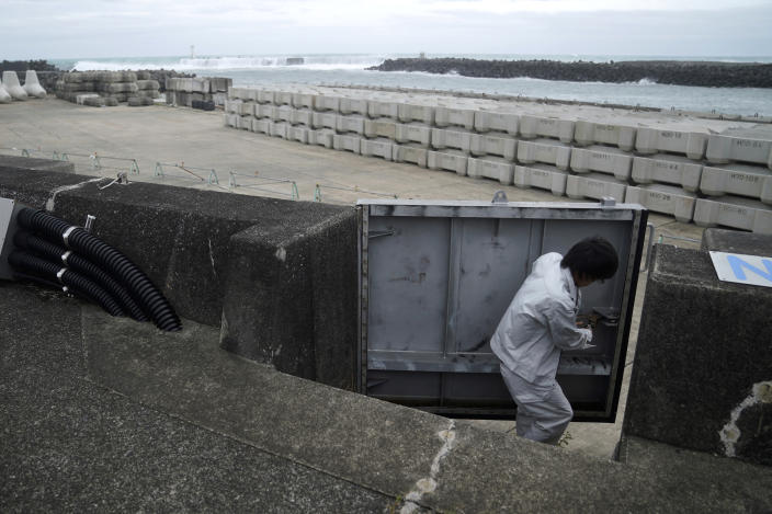 A Kiho town official closes a door of a coastal levee as Typhoon Hagibis approaches at a port in town of Kiho, Mie Prefecture, Japan Friday, Oct. 11, 2019. A powerful typhoon is advancing toward the Tokyo area, where torrential rains are expected this weekend. (AP Photo/Toru Hanai)