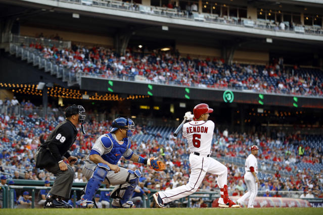 Washington Nationals' Anthony Rendon, right, hits a ground rule double in front of New York Mets catcher Wilson Ramos and home plate umpire Cory Blaser in the first inning of a baseball game, Wednesday, May 15, 2019, in Washington. Adam Eaton scored on the play. (AP Photo/Patrick Semansky)