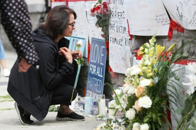 A woman prays at a makeshift memorial for victims of the van massacre in Toronto, which left 10 dead