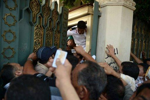 Egyptian guards try to close the gate of presidential palace in Cairo