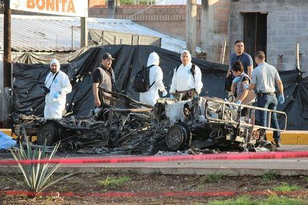 Forensic technicians stand at a crime scene next to the burnt wreckage of a military vehicle, after what local media said was an ambush by gunman on a military convoy to free an injured fellow gunman from an ambulance, in Culiacan, in Sinaloa state, Mexico, September 30, 2016. REUTERS/Jesus Bustamante