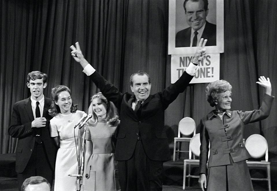 """<span class=""""caption"""">Richard Nixon, celebrating his election on Nov. 7, 1968, campaigned against a backdrop of racial inequality, civic unrest and polarized politics.</span> <span class=""""attribution""""><a class=""""link rapid-noclick-resp"""" href=""""https://www.gettyimages.com/detail/news-photo/republican-presidential-candidate-richard-nixon-is-news-photo/1157399033?adppopup=true"""" rel=""""nofollow noopener"""" target=""""_blank"""" data-ylk=""""slk:AFP via Getty Images"""">AFP via Getty Images</a></span>"""