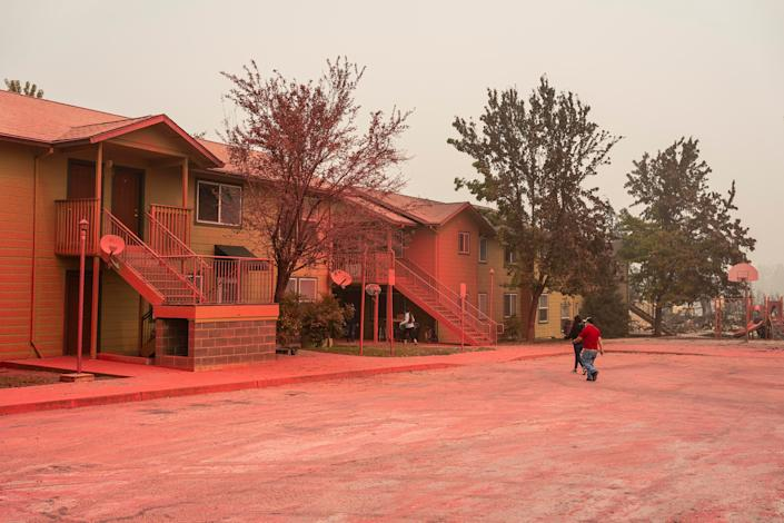 Residents collect belongings from a housing structure saved by fire retardant in a neighborhood largely destroyed by wildfire on September 13, 2020 in Talent, Oregon.